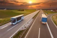 Camión y autobús en la falta de definición de movimiento en la carretera en la puesta del sol Fotos de archivo libres de regalías
