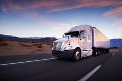 Camión y carretera en la puesta del sol - fondo del transporte Imagen de archivo