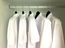 Camice bianche che appendono sugli scaffali fotografia stock