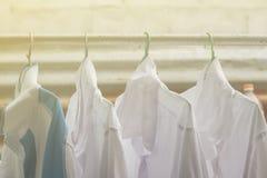 Camice che appendono sopra sulla ferrovia o sui vestiti aperti all'aperto il giorno della lavanderia fotografie stock
