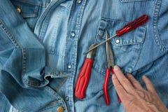 Camice del denim, strumenti ed una mano Immagine Stock Libera da Diritti