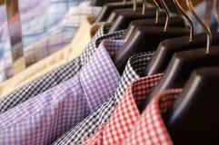 Camice di plaid del ` s degli uomini nei colori differenti sui ganci Fotografie Stock