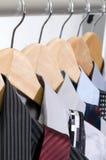 Camice e legami di vestito sui ganci. Fotografia Stock