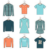 Camice, magliette felpate e vestiti del profilo sui ganci su fondo bianco Fotografie Stock Libere da Diritti