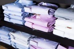 Camice sugli shelfs nel boutique degli uomini Fotografia Stock Libera da Diritti