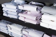 Camice sugli shelfs nel boutique degli uomini Immagini Stock Libere da Diritti