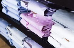 Camice sugli shelfs nel negozio di vestiti degli uomini Fotografie Stock