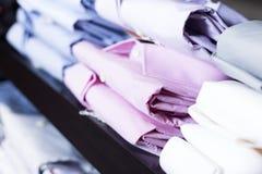 Camice sugli shelfs nel negozio di vestiti degli uomini Immagini Stock