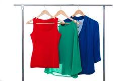Camice variopinte del ` s delle donne sui ganci di legno su fondo bianco RGB Immagini Stock Libere da Diritti