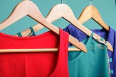 Camice variopinte del ` s delle donne sui ganci di legno su fondo blu RGB Immagini Stock Libere da Diritti