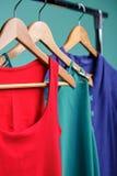 Camice variopinte del ` s delle donne sui ganci di legno su fondo blu RGB Fotografia Stock