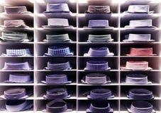 Camice variopinte piegate sullo scaffale dei vestiti Fotografia Stock