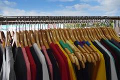 Camice variopinte sui ganci di legno nel fondo del deposito o del mercato Fotografia Stock Libera da Diritti