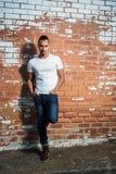 Camicia bianca d'uso dell'uomo bello e pendere contro un muro di mattoni Fotografia Stock Libera da Diritti