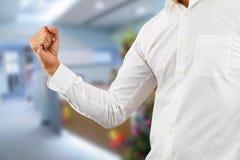 Camicia bianca d'uso dell'uomo di affari che alza pugno giusto su con allegro sul fondo vago dell'ufficio immagini stock