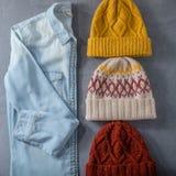 Camicia dei jeans e tre cappelli di inverno Fotografie Stock