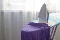 Camicia e ferro sul ferro della tavola da stiro fotografia stock libera da diritti