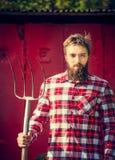 Camicia a quadretti rossa del giovane agricoltore barbuto con la vecchia forca che esamina macchina fotografica Immagini Stock