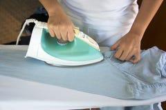 Camicia rivestente di ferro della donna sulla tavola da stiro Fotografia Stock Libera da Diritti