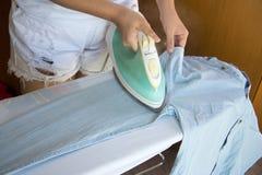 Camicia rivestente di ferro della donna sulla tavola da stiro Fotografia Stock