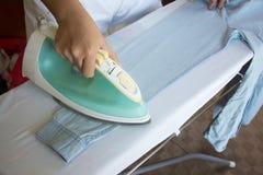 Camicia rivestente di ferro della donna sulla tavola da stiro Fotografie Stock Libere da Diritti