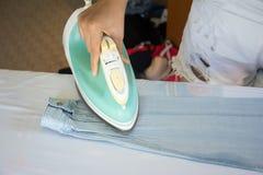 Camicia rivestente di ferro della donna sulla tavola da stiro Immagine Stock