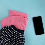 Camicia rosa, gonna di tela della marina, telefono cellulare su fondo blu-chiaro fotografie stock