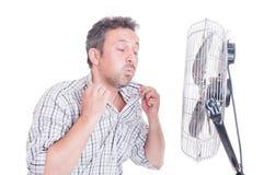 Camicia sudata di apertura dell'uomo davanti alla ventola di raffreddamento immagini stock libere da diritti