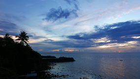 Camiguin Island Sunset. A colorful sunset video from the beautiful Camiguin Island shores. A local fishing boat can be seen in the distance. Presented in real stock footage