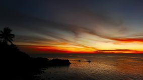 Camiguin Island Sunset 14. A dark sunset video from Camiguin Island. Silhouettes of palm trees on the shore and local fishing boats cruising near the coast can stock video footage