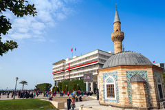 Camii mosque on Konak square, Izmir, Turkey. Izmir, Turkey - February 5, 2015: Tourists walking near ancient Camii mosque on Konak square, Izmir, Turkey Royalty Free Stock Image