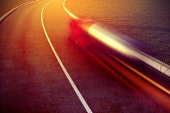 Camión rápido en la falta de definición de movimiento de la carretera de asfalto Foto de archivo libre de regalías