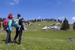 """Caminando caminantes del †""""que caminan en alza en naturaleza de la montaña y que señalan en pico de montaña, el día soleado Imagen de archivo libre de regalías"""