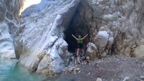 Caminando en montañas, un turista femenino alegre en la ropa protectora que lleva una forma de vida activa está en un extremo metrajes