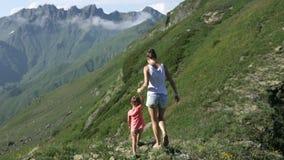 Caminando a la mujer con la hija en la excursión del viaje que camina en montaña ajardine almacen de video