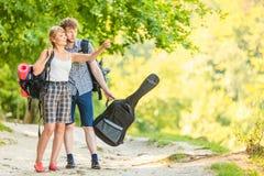 Caminando pares jovenes con la guitarra haga excursionismo al aire libre Imágenes de archivo libres de regalías