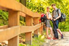 Caminando pares jovenes con la guitarra haga excursionismo al aire libre Fotografía de archivo libre de regalías