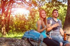 Caminando pares jovenes de la comida campestre bebe el café Imagen de archivo libre de regalías