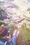 Caminante acertado de la mujer que usa smartphone en el borde del acantilado en el top de la montaña Isla de Bali imagenes de archivo