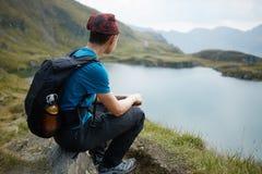 Caminante adolescente por el lago en las montañas Foto de archivo libre de regalías