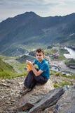 Caminante adolescente que descansa sobre una roca Fotos de archivo libres de regalías