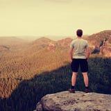 Caminante adulto en camisa gris y pantalones oscuros Hombre alto en el pico del acantilado de la piedra arenisca que mira abajo a Fotos de archivo