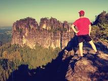 Caminante adulto en camisa roja y pantalones oscuros Hombre en el acantilado de la piedra arenisca Foto de archivo
