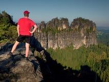 Caminante adulto en camisa roja y pantalones oscuros Hombre en el acantilado de la piedra arenisca Fotos de archivo libres de regalías