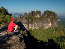 Caminante adulto en camisa roja y pantalones oscuros Hombre en el acantilado de la piedra arenisca Imagen de archivo libre de regalías