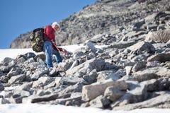 Caminante caucásico maduro que sube con la mochila en montaña de la cuesta escarpada en la estación de verano Foto de archivo