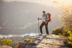 Caminante con el bebé que se coloca en el acantilado Foto de archivo libre de regalías