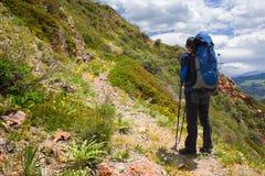Caminante con el morral en montañas Fotos de archivo