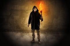 Caminante con la antorcha ardiente delante del concepto desmenuzable de la pared imagen de archivo libre de regalías