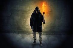 Caminante con la antorcha ardiente delante del concepto desmenuzable de la pared fotografía de archivo libre de regalías